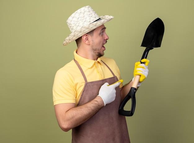 Jonge tuinman man met jumpsuit en hoed in werkhandschoenen houden schop wijzend met wijsvinger naar het kijken verbaasd