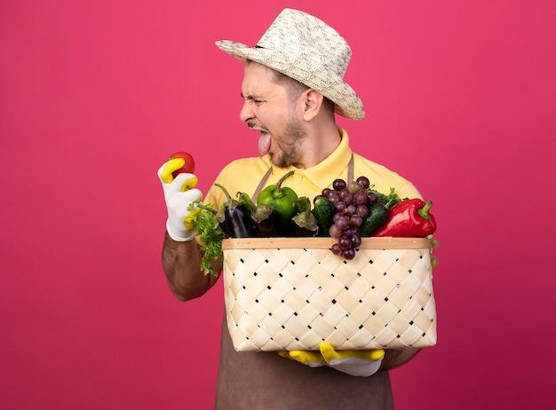 Jonge tuinman man met jumpsuit en hoed in werkhandschoenen met krat vol groenten kijken naar verse tomaat in de hand met walging expressie