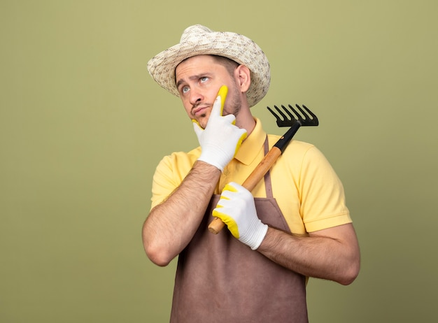 Jonge tuinman man met jumpsuit en hoed in werkhandschoenen met mini hark opzij kijken met hand op kin denken