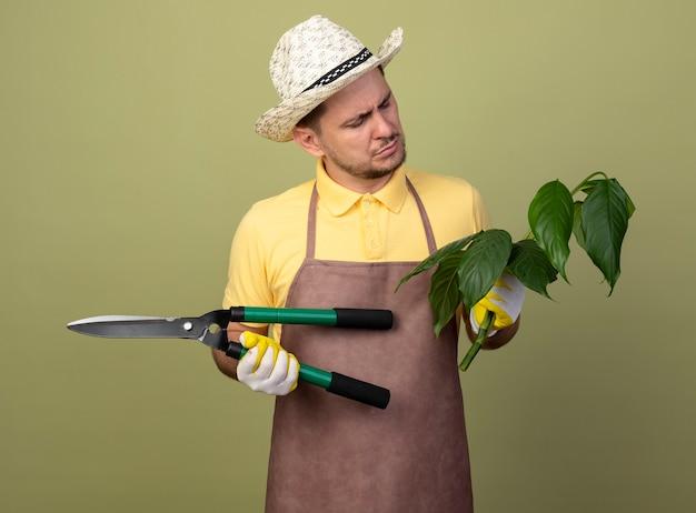 Jonge tuinman man met jumpsuit en hoed in werkhandschoenen met plant en heggenschaar op zoek met ernstig gezicht