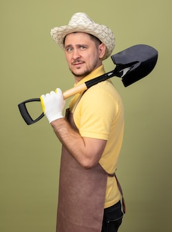 Jonge tuinman man met jumpsuit en hoed in werkhandschoenen met schop op schouder op zoek zelfverzekerd