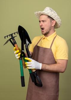 Jonge tuinman man met jumpsuit en hoed in werkhandschoenen met tuinieren apparatuur kijken ze verward en verrast