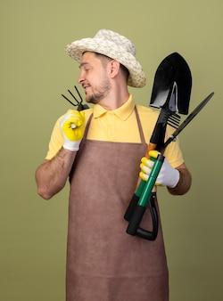 Jonge tuinman man met jumpsuit en hoed in werkhandschoenen met tuinieren apparatuur terugkijkend met een glimlach op het gezicht