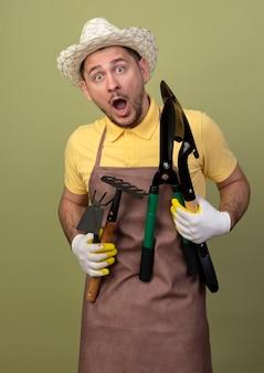 Jonge tuinman man met jumpsuit en hoed in werkhandschoenen met tuinieren apparatuur verbaasd en verrast