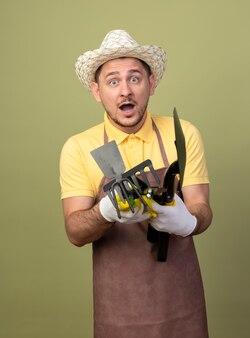 Jonge tuinman man met jumpsuit en hoed in werkhandschoenen met tuinieren apparatuur verrast