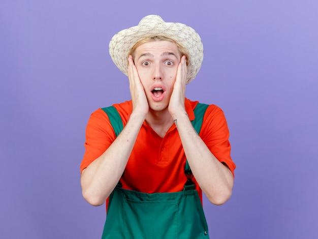 Jonge tuinman man met jumpsuit en hoed kijken camera ongerust staande over paarse achtergrond