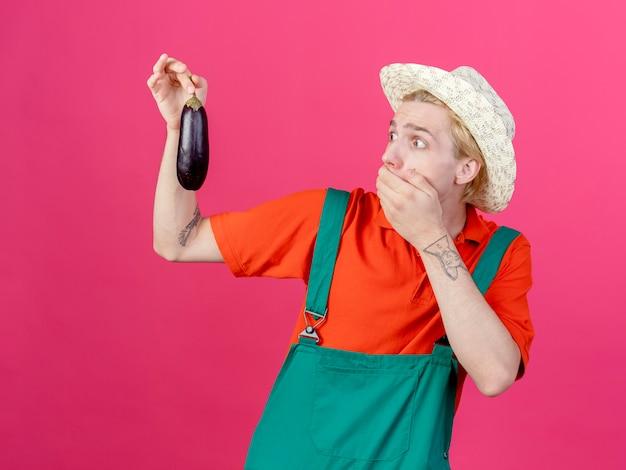 Jonge tuinman man met jumpsuit en hoed met aubergine te kijken naar het wordt geschokt