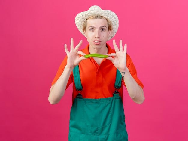 Jonge tuinman man met jumpsuit en hoed met groene chili peper glimlachen