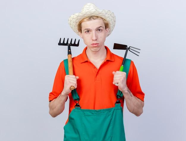 Jonge tuinman man met jumpsuit en hoed met mini hark en houweel kijken camera met ernstig gezicht staande op witte achtergrond