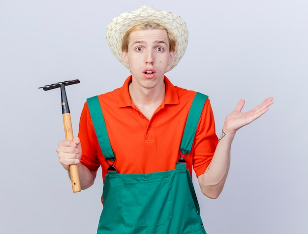 Jonge tuinman man met jumpsuit en hoed met mini hark kijken camera schouderophalend schouders wordt verward staande op witte achtergrond