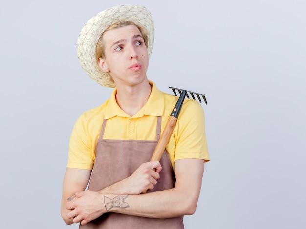 Jonge tuinman man met jumpsuit en hoed met mini hark opzij kijkend verbaasd