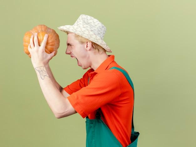 Jonge tuinman man met jumpsuit en hoed met pompoen schreeuwen met boos gezicht staande zijwaarts over lichte achtergrond