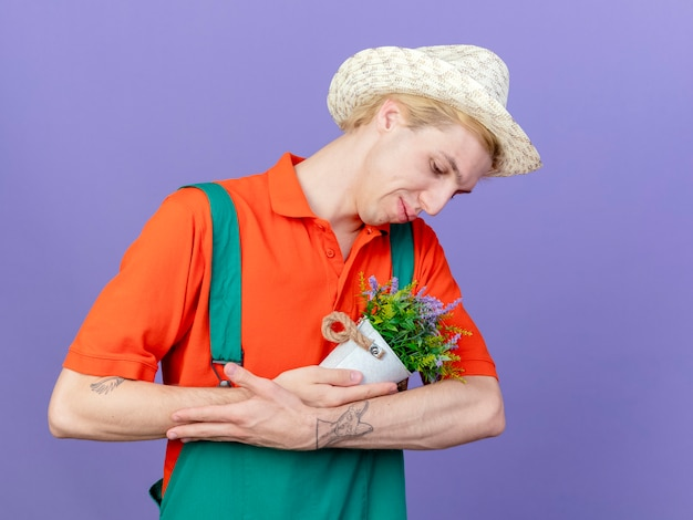 Jonge tuinman man met jumpsuit en hoed met potplant als baby