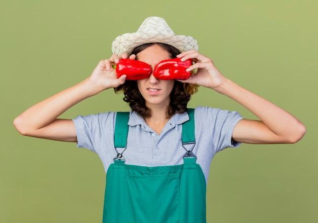 Jonge tuinman man met jumpsuit en hoed met rode paprika