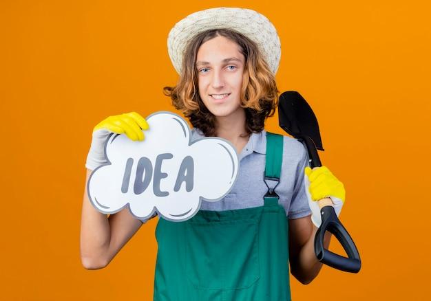 Jonge tuinman man met jumpsuit en hoed met schop en tekstballon teken