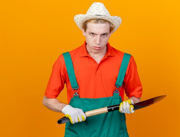 Jonge tuinman man met jumpsuit en hoed met schop met ernstig gezicht