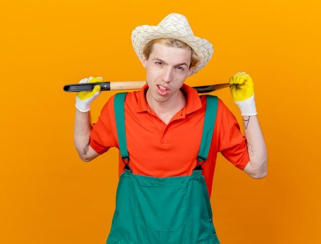Jonge tuinman man met jumpsuit en hoed met schop met zelfverzekerde uitdrukking