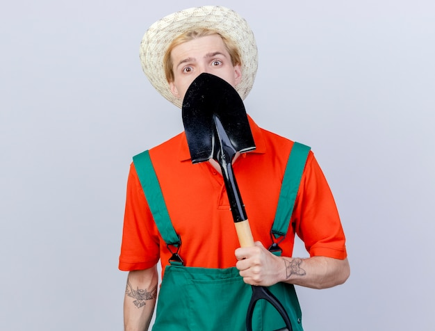 Jonge tuinman man met jumpsuit en hoed met schop zijn gezicht achter wordt verward staande op een witte achtergrond te houden