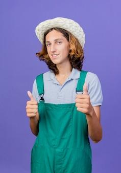 Jonge tuinman man s dragen jumpsuit en hoed glimlachend duimen opdagen
