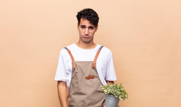 Jonge tuinman man verdrietig en janken met een ongelukkige blik, huilen met een negatieve en gefrustreerde houding