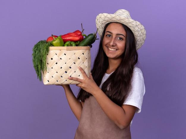 Jonge tuinman meisje in schort en zomer hoed bedrijf krat vol groenten met blij gezicht glimlachend vrolijk staande over paarse muur