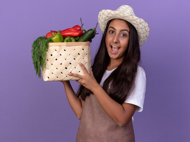 Jonge tuinman meisje in schort en zomer hoed bedrijf krat vol groenten met blij gezicht staande over paarse muur