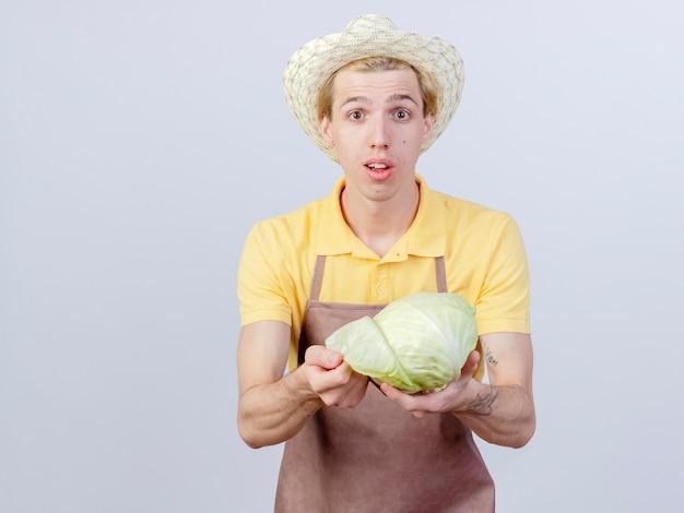 Jonge tuinman met een jumpsuit en een hoed die kool vasthoudt met een glimlach op het gezicht