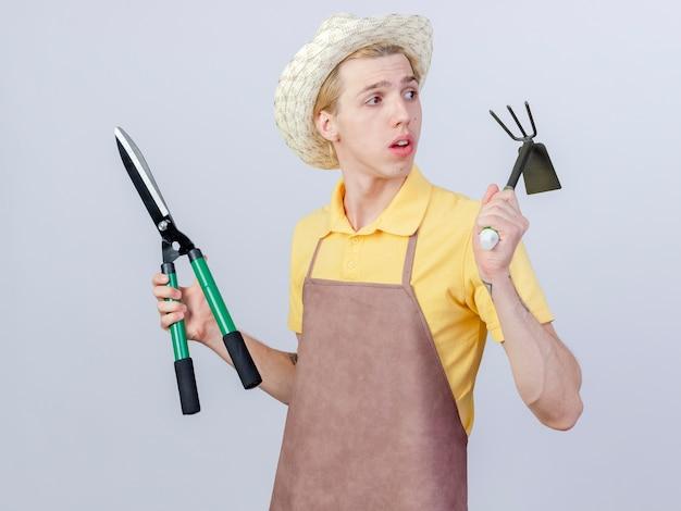 Jonge tuinman met een jumpsuit en een hoed met een mat en een heggenschaar die verbaasd opzij kijkt