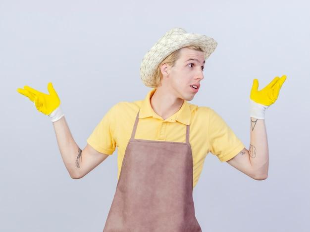 Jonge tuinman met een jumpsuit en hoed in rubberen handschoenen die opzij kijkt terwijl hij zijn handen naar de zijkanten spreidt en glimlacht