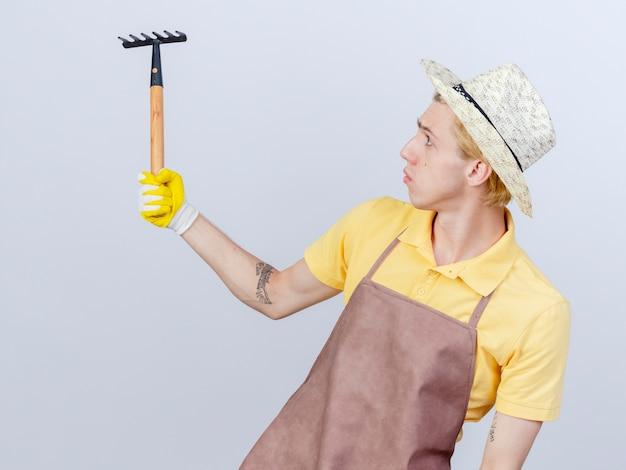 Jonge tuinman met een jumpsuit en hoed in rubberen handschoenen met een minihark die er met een serieus gezicht naar kijkt