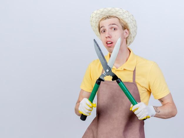 Jonge tuinman met jumpsuit en hoed in rubberen handschoenen met heggenschaar met een glimlach op het gezicht