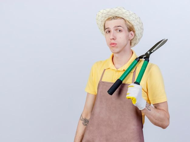 Jonge tuinman met jumpsuit en hoed in rubberen handschoenen met heggenschaar met een serieus gezicht