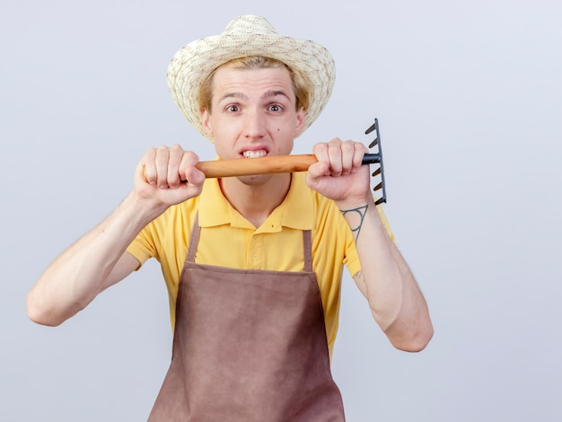 Jonge tuinman met jumpsuit en hoed met minihark is ontevreden dis
