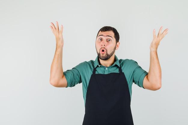 Jonge tuinman steekt handen op met vragende manier in t-shirt, schort en kijkt hulpeloos. vooraanzicht.