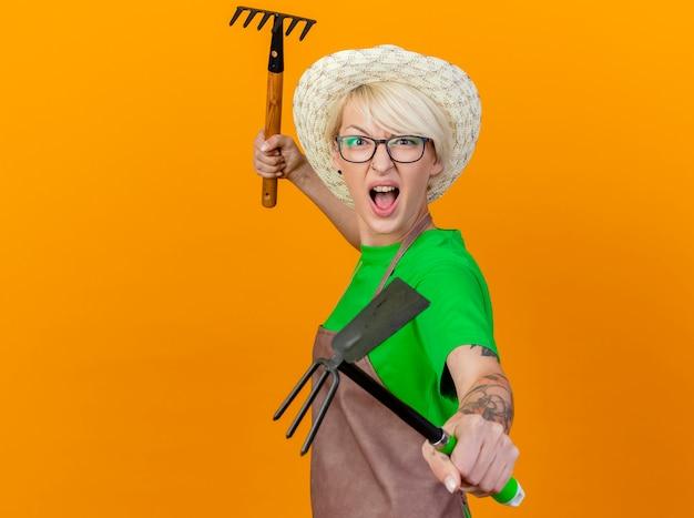 Jonge tuinman vrouw met kort haar in schort en hoed met mattock en mini hark kijken camera met boos gezicht schreeuwen staande over oranje achtergrond