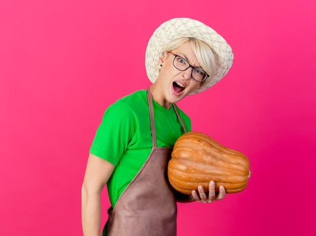 Jonge tuinman vrouw met kort haar in schort en hoed met pompoen