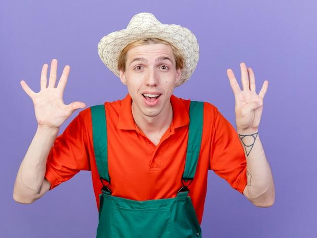 Jonge tuinmanmens die jumpsuit en hoed draagt die nummer negen toont