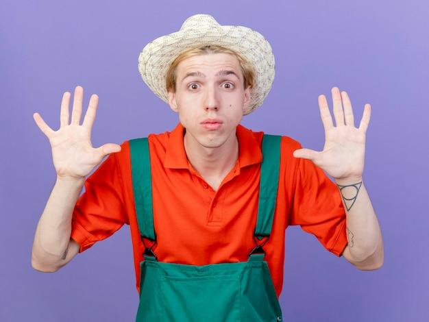 Jonge tuinmanmens die jumpsuit en hoed draagt die nummer tien toont die wordt verrast