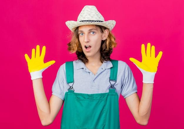 Jonge tuinmanmens die jumpsuit en hoed draagt die rubberhandschoenen draagt die palmen opheft