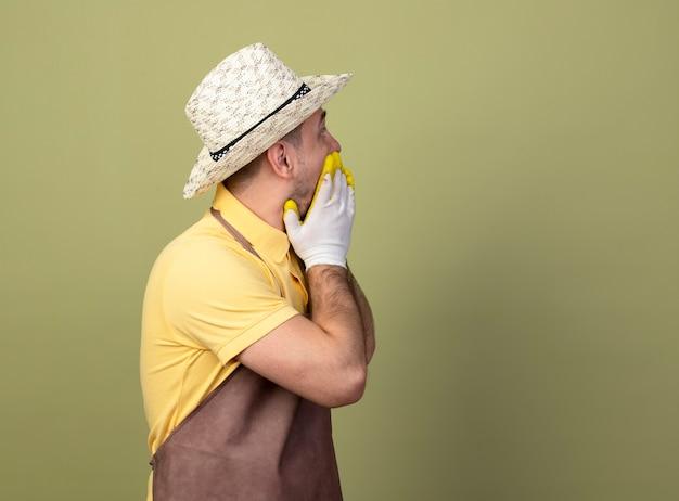 Jonge tuinmanmens die jumpsuit en hoed in werkhandschoenen draagt die opzij wordt geschokt die mond behandelt met handen
