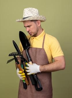 Jonge tuinmanmens die jumpsuit en hoed in werkhandschoenen draagt die tuiniermateriaal houdt die hen met ernstig gezicht bekijkt dat zich over lichte muur bevindt