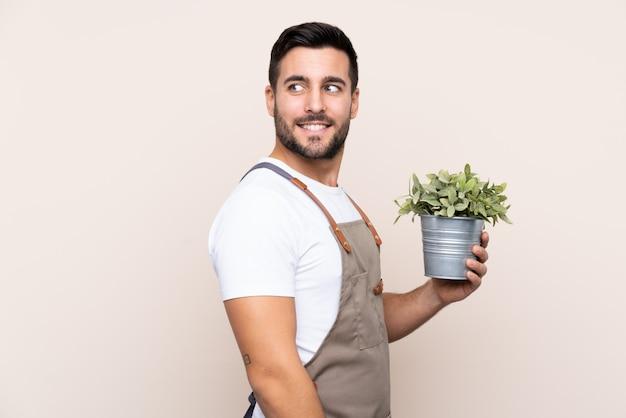 Jonge tuinmanmens over geïsoleerde muur