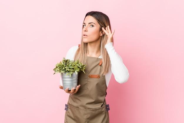 Jonge tuinmanvrouw die een installatie houdt proberend om een roddel te luisteren.