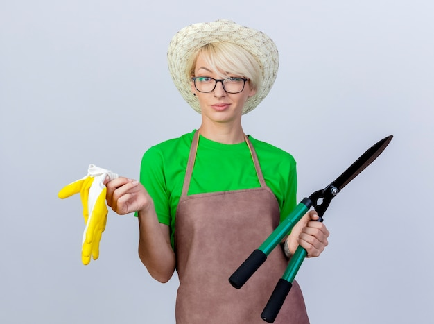 Jonge tuinmanvrouw met kort haar in schort en hoed met heggenschaar en rubberen handschoenen die zelfverzekerd glimlachen smiling