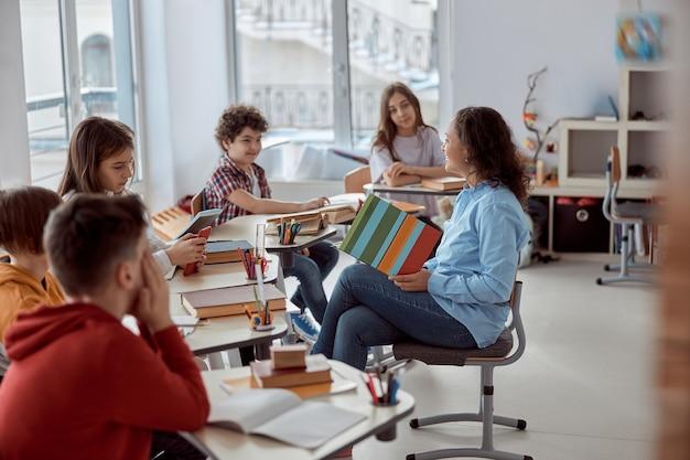 Jonge tutor leert haar student te lezen. basisschoolkinderen zittend op een bureau en het lezen van boeken in de klas. Premium Foto