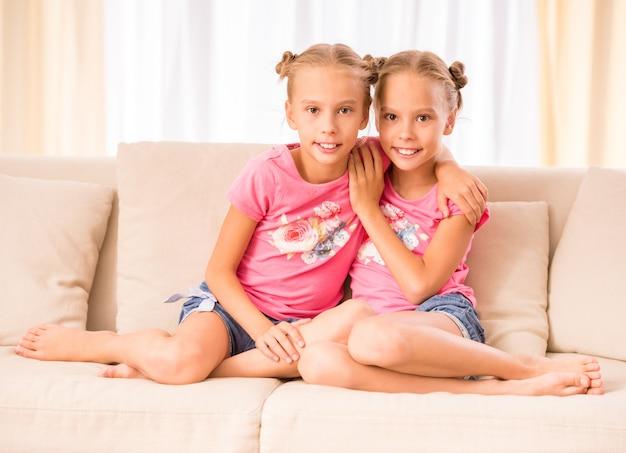 Jonge tweelingen omhelzen elkaar op een bank.