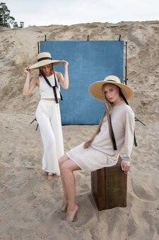Jonge tweelingmeisjes met lang blond haar poseren in zandgroeve in elegante witte, beige kleding