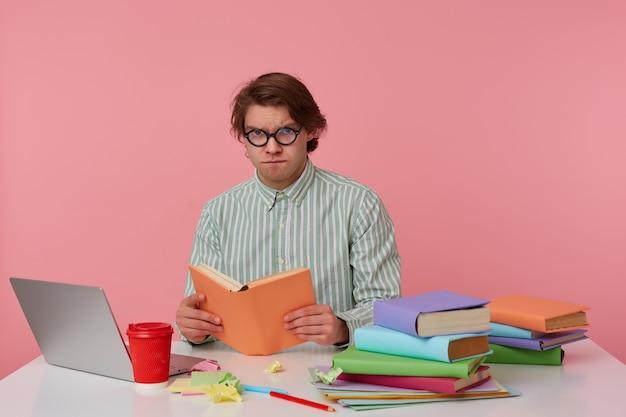 Jonge twijfelende man met bril draagt in shirt, zit bij de tafel en werkt met notitieboekje, voorbereid op examen, boek leest, ziet er verdrietig en moe uit, geïsoleerd op roze achtergrond.