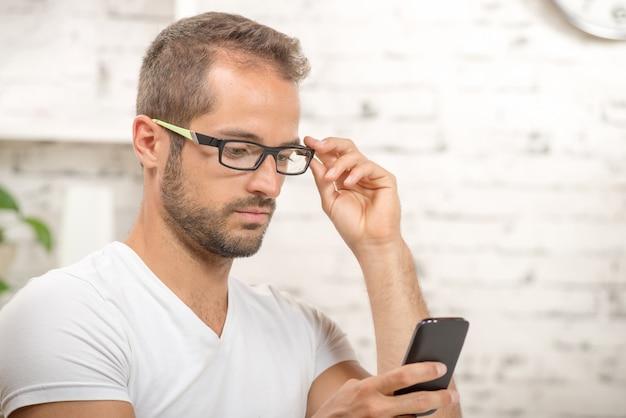 Jonge uitvoerende macht die zijn mobiel kijkt