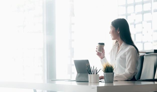 Jonge uitvoerende zakenvrouw koffiekopje houden en ontspannen zittend aan haar bureau tijdens het werk.